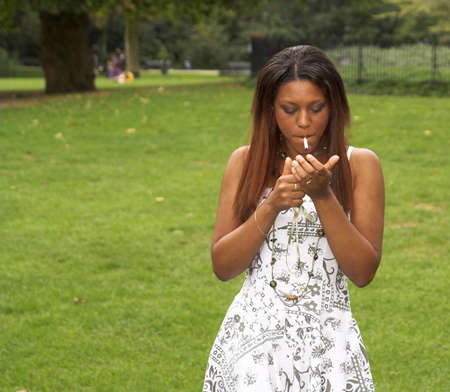 Pretty black girl lighting up her cigarette in a park photo