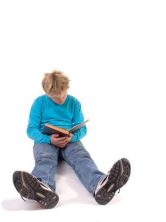 sitting teenager boy reading antique book; isolated on white background
