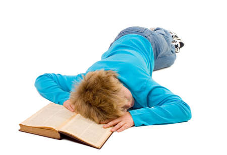 *** note for inspectors: the book is very old (1915), the text in the book is even older (~1830) thus no copyright issue with recognizable text***  Tired teenager boy fallen asleep on his book; isolated on white