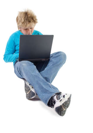 blonde boy working with laptop; isolated on white