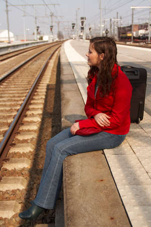 wind blown hair: Young brunette woman waiting for a train on a railway station Stock Photo