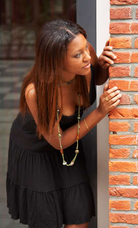 Pretty brunette girl peeking around the corner