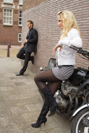 pretty blond girl and her boyfriend standing apart from each other photo