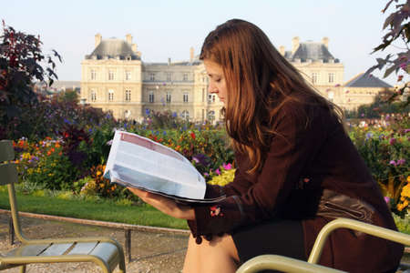 Pretty girl reading magazine in Luxembourg garden (Paris). Late afternoon sun. Autumn colors. photo