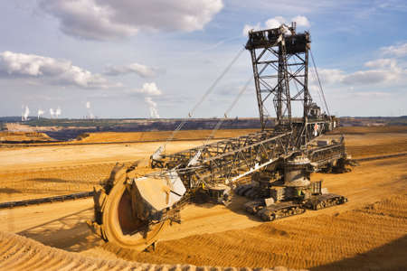 Giant bucket wheel excavator taking away the layers of ground before digging the brown coal. Largest open pit lignite mine in Europe. Power stations at horizon transform the coal to electricity.