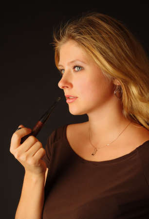 smoking pipe: Pretty blond girl with pipe against dark background