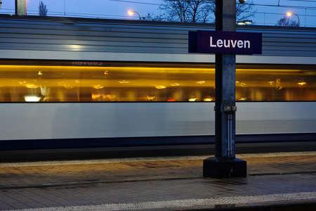 leuven: Train moving along platform in twilight (station Leuven) Stock Photo