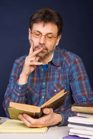 Mature man in glasses reading old book photo