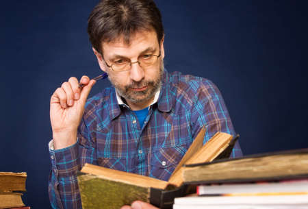 Mature man in glasses reading his book Stock Photo
