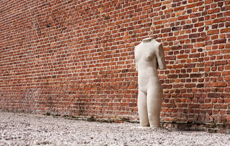 redbrick: Lonely sculpture standing next to red-brick wall Stock Photo