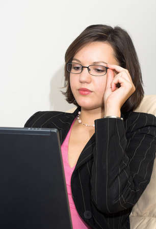 Young attractive business lady sitting on a sofa with laptop touches her glasses; photo