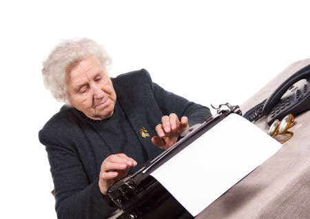 old woman typing on old typewriter, isolated on white photo
