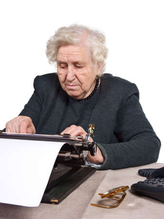 Old lady working an old-fashioned way with typewriter photo