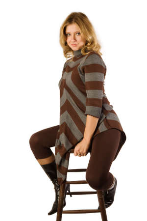 pretty blond girl sitting on bar chair; isolated on white photo