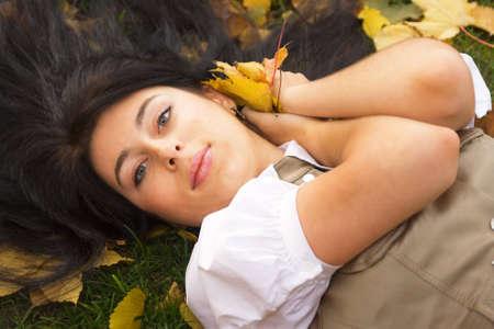 Chica bonita morena de descanso en un parque de oto�o Foto de archivo - 4143672