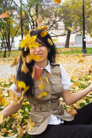 throw up: young brunette woman enjoying nice autumn weather in a park