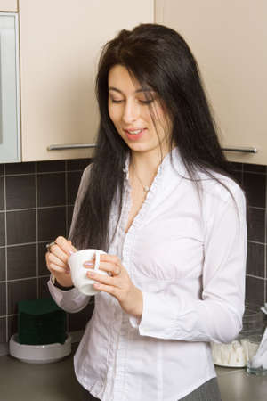 kitchenette: Pretty brunette girl at coffee break in the office