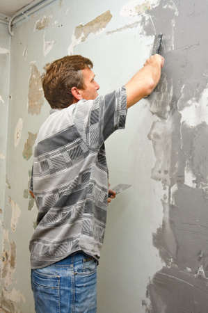 Plasterer at work doing indoor house repair with plaster Stock Photo