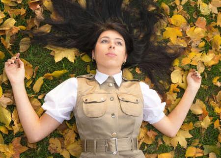 Pretty brunette girl resting in an autumn park photo