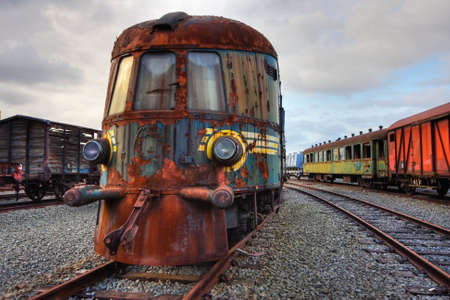 wood railroad: Abandoned railroad engine and carriages standing on rusty rails (an HDR image)