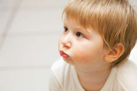 puffed cheeks: Indoor photo of little blond boy with puffed out cheeks