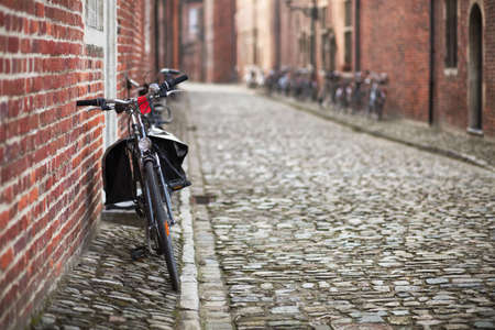leaned: Bicycle leaned to a wall of brick medieval house; cobblestone pavement