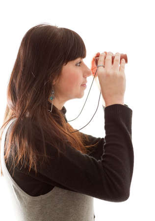 far away look: brunette girl looking in binoculars; isolated on white