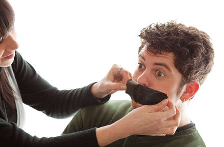 duct tape: girl sticking a piece of gaffer tape on young mans mouth