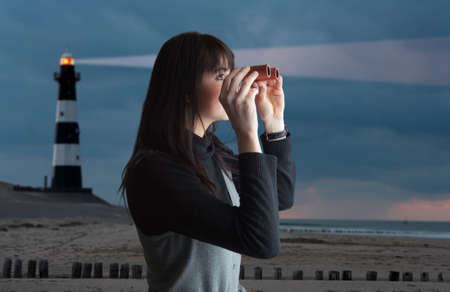 Brunette woman looking via binoculars; lighthouse on background photo