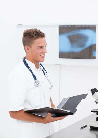 auscultoscope: Smiling young doctor with phonendoscope having good news about patient diagnosis;