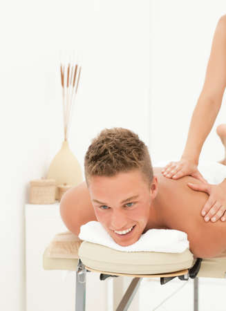 back rub: Happy young man enoying massage session in spa resort