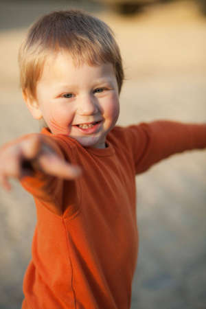 sunglight: Laughing little boy in orange evening sunglight; blurred background