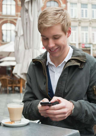 Young blond handsome smiling man typing a text message on his mobile phone Stock Photo