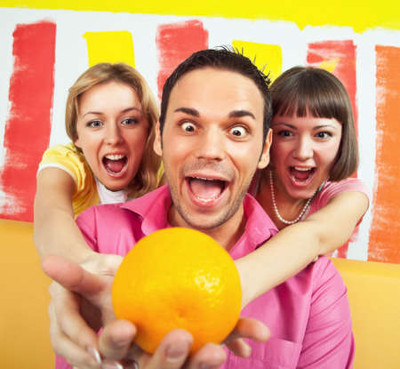 Group of three people is very emotional about an orange; room painted in vivid colors photo