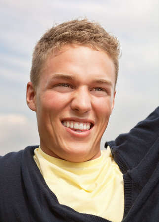 Smiling young blond guy outdoors; head and shoulders portrait Stock Photo - 6203917