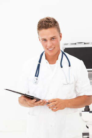 auscultoscope: Young blond handsome doctor having good news Stock Photo