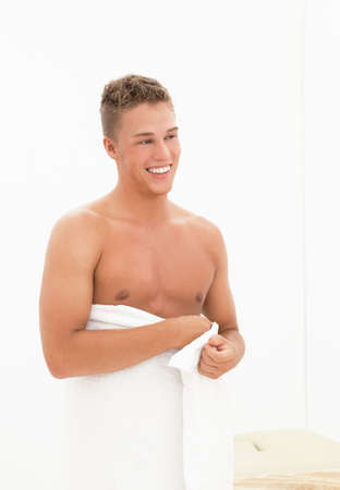 Young blond smiling handsome man wrapped in towel photo
