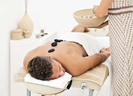 Young man enjoying the treatment in spa salon photo