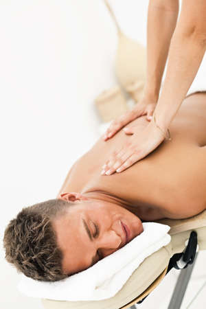 back rub: Young man enjoying the treatment in spa salon