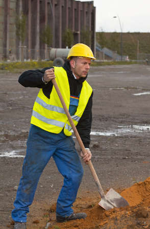 Construction worker in workwear and in yellow hardhat digging sand with shovel