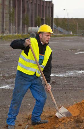 Trabajador de la construcción en ropa de trabajo y en hardhat amarillo arena de excavación con pala Foto de archivo