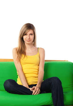 Pretty young blond woman sitting on green sofa