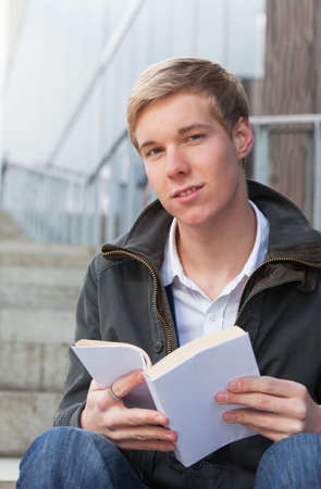 handome: young blond handsome man sitting on stairs outdoors with book  Stock Photo