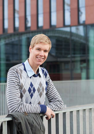 hist: Happy young blond man waiting for hist train at railway station Stock Photo