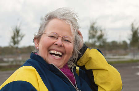 Senior woman happily laughing outdoor, in a windy overcast day Stock Photo
