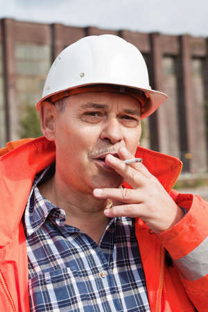 Senior engineer in reflective workwear and in white hardhat smoking outdoor