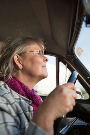 Happy senior woman driving an oldtimer car