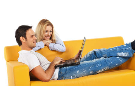 Happy young man and woman sitting together and looking at computer screen Stock Photo