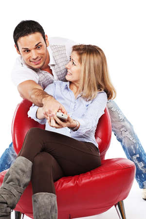 Young man and woman are fighting for TV remote because they can't agree what program to watch Stock Photo - 7771520