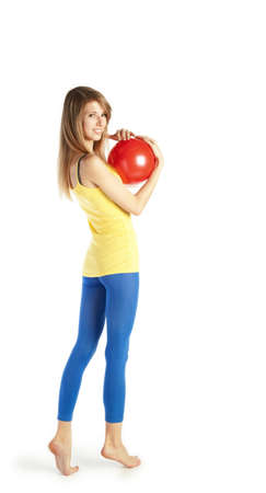 Young happy blond woman standing on tiptoe and holding red ball photo